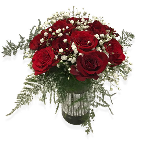 This lovely arrangement of Red Roses are bundled up love and babies breath wrapped with lush greens floating on a bed of river rock in a clear cylinder vase.<br/><br>